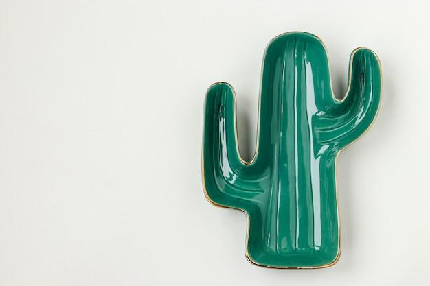Piatto a forma di cactus verde su sfondo bianco per servire insalate e snack, copia spazio, orientamento orizzontale, vista dall'alto