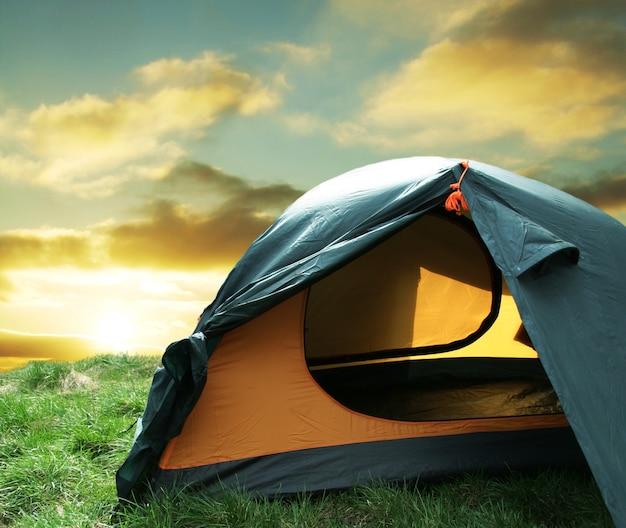 Tenda da campeggio verde su prati soleggiati