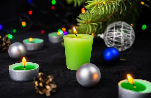 Candele verdi accanto all'albero di natale, luci e decorazioni natalizie.