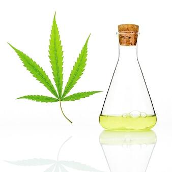 Foglie di cannabis verde con una bottiglia di vetro di riflessione olio di cannabis isolato su bianco