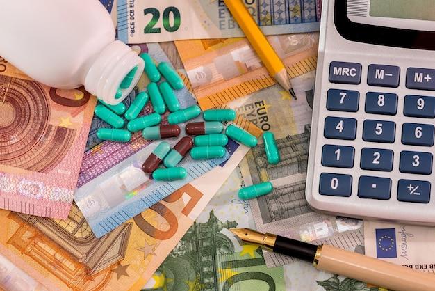Capsule verdi disperse su banconote in euro e calcolatrice