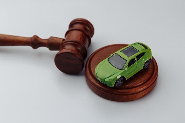 Martelletto verde del giudice e dell'automobile su una parete bianca. concetto di vendita di un'auto tramite asta o sentenza di incidente
