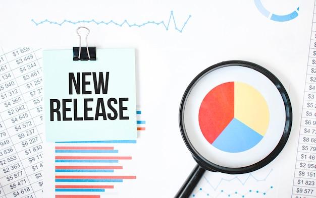 Carta verde sul blocco note bianco e sulla lente d'ingrandimento sulla documentazione finanziaria. testo nuova versione. concetto di affari