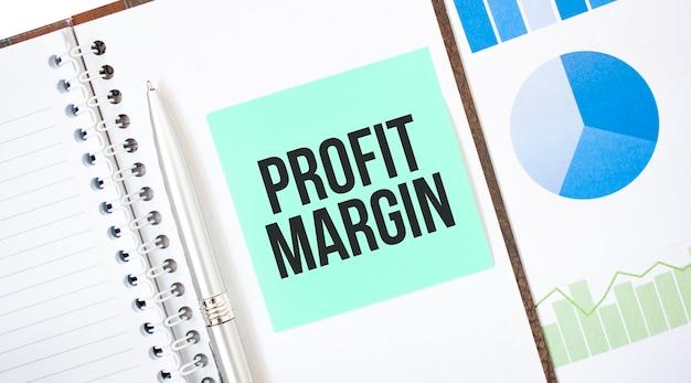 Carta verde sul blocco note bianco. testo margine di profitto. concetto di affari