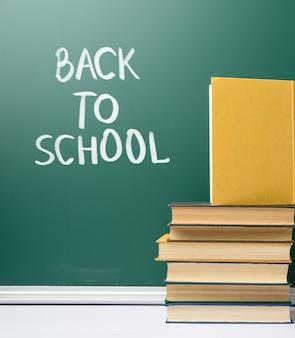 Consiglio scolastico di gesso verde e pila di libri, torna a scuola, copia dello spazio