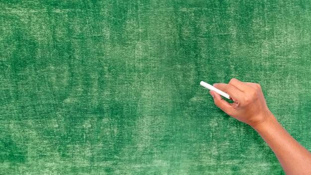 Lavagna verde e mano che tiene il gesso scrivono su lavagna verde
