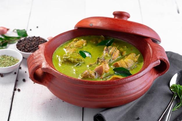 Pollo al curry verde con materie prime che è disposto in un vasetto di terracotta