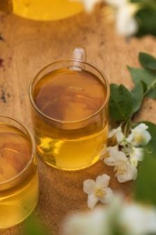 Tè verde cinese al gelsomino in tazza con fiori di gelsomino