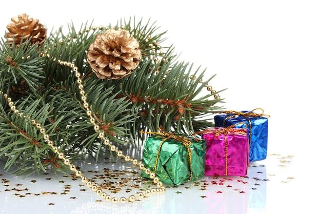 Albero di natale verde con regalo e coni isolati su bianco