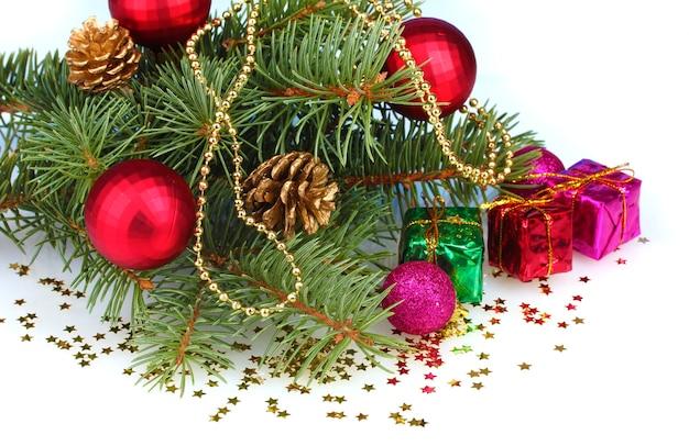 Albero di natale verde con regalo, giocattolo e coni isolati su bianco