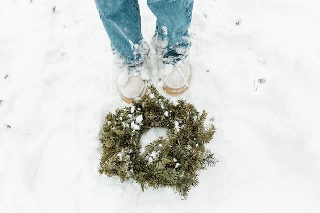 Corona di natale verde sulla neve. bella ragazza che gode dell'inverno all'aperto.