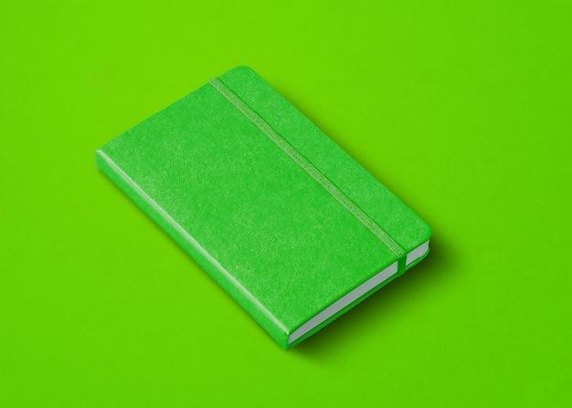 Modello di taccuino chiuso verde isolato su sfondo colorato
