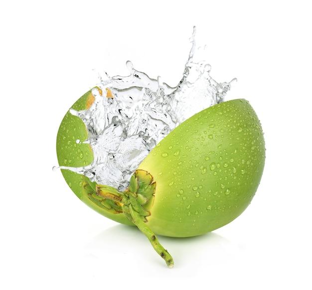 Cocco verde con spruzzi d'acqua isolato su bianco