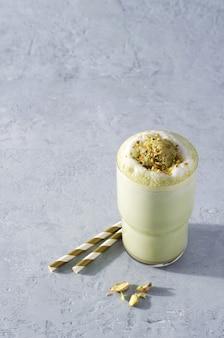 Latte matcha al caffè verde con schiuma cosparsa di noci su uno sfondo di cemento con spazio per la copia
