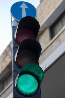 Colore verde sulla lente del semaforo in città con il segno della freccia in avanti dritto sopra, sfondo del cielo blu. primo piano dei segnali stradali sulla strada. segno di freccia blu durante il tramonto.