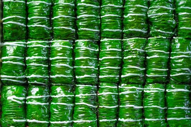 Baklava da dessert turco di colore verde disposto in file