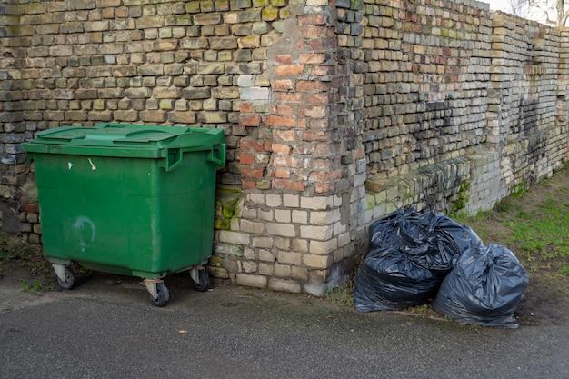 Contenitore verde e mucchio di sacchi della spazzatura