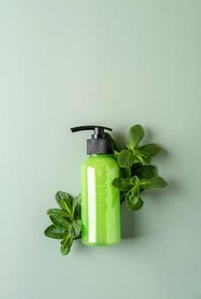 Flacone cosmetico verde con dispenser, menta fresca su bakground verde pastello. concetto di cosmetici biologici. modello di contenitore cosmetico con posto per il testo. prodotto per la cura della pelle naturale.
