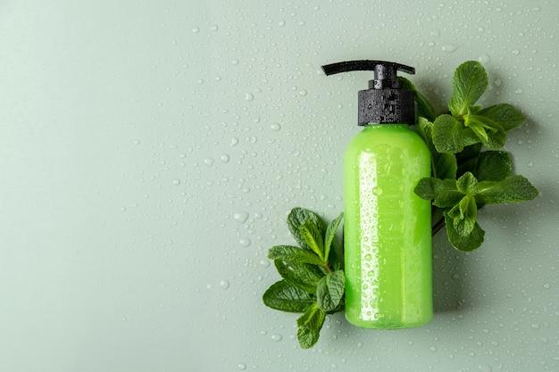 Flacone cosmetico verde con dispenser, menta fresca e gocce d'acqua. concetto di cosmetici biologici. modello di contenitore cosmetico con posto per il testo. prodotto per la cura della pelle naturale.