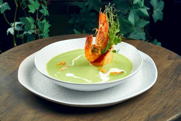 Zuppa di piselli cremosa verde con gamberetti e cozze su una superficie di legno.