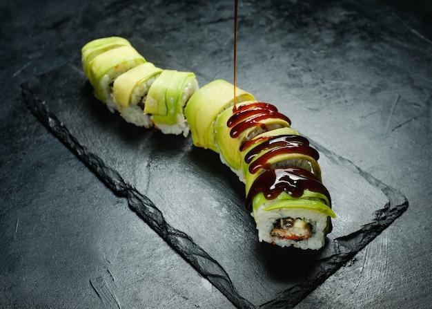 Rotoli di sushi di avocado con drago verde su sfondo scuro con salsa unagi che versa dall'alto