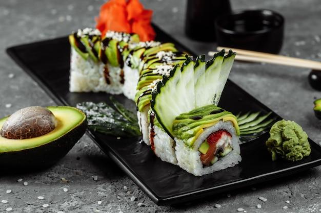 Rotolo di sushi drago verde con anguilla, avocado, cetriolo e zenzero, accompagnato da gamberi in tempura fritti. frutti di mare sani di sushi di riso asiatico tradizionale.