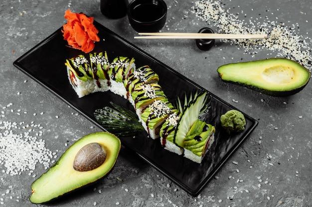 Rotolo di sushi al drago verde con anguilla, avocado, cetriolo e zenzero, accompagnato da gamberi fritti in tempura