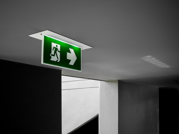 Segnale di uscita di emergenza verde che pende dal soffitto incandescente nel corridoio buio vicino alla porta antincendio nell'edificio