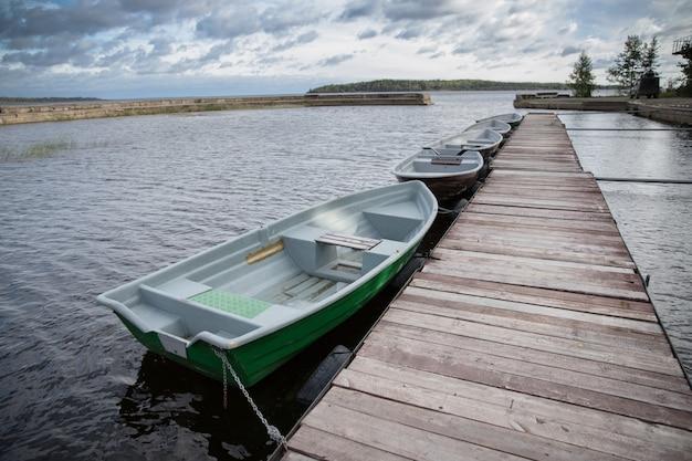 Barche vuote verdi sul lago lungo il molo in legno, cielo nuvoloso autunnale sullo sfondo.