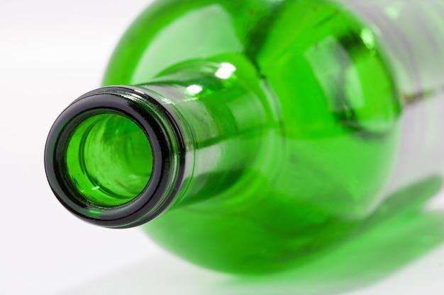 Verde bottiglia di vino vuota posa isolata su bianco