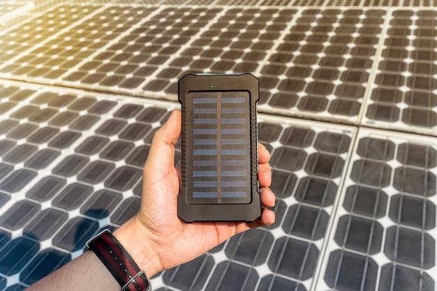 Energia verde, cella solare fotovoltaica con la mano. mobile power bank in mano sullo sfondo di grandi pannelli solari. caricatore del telefono ad energia solare
