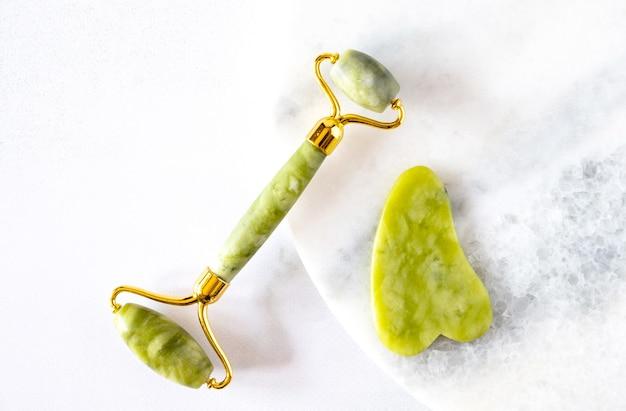 Rullo facciale verde e massaggiatore gua sha realizzato con pietra naturale di nefrite di giada su sfondo di marmo