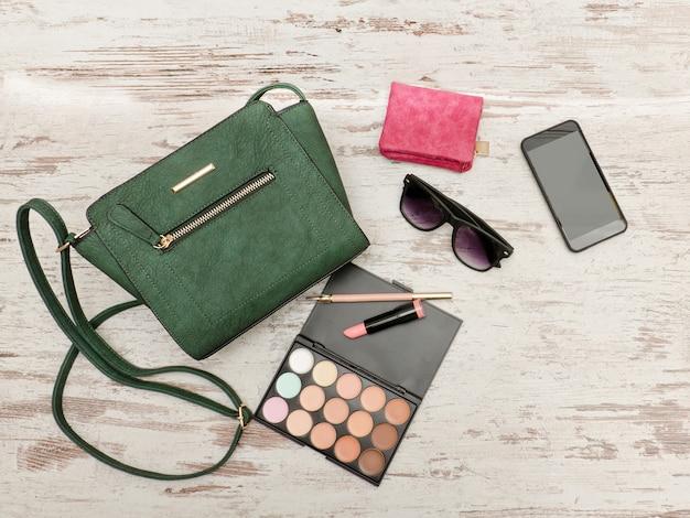 Borsa femmina verde, telefono, tavolozza di ombretti, telefono, occhiali da sole e rossetto su un fondo di legno.