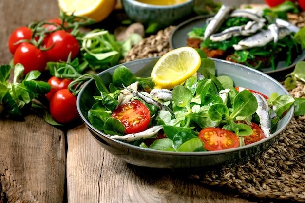 Insalata di campo verde con acciughe sott'aceto e pomodorini, servita in una ciotola blu con limone e olio d'oliva su tovagliolo di paglia sul vecchio tavolo di legno