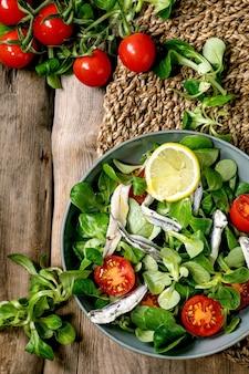 Insalata di campo verde con acciughe sottaceto o filetto di sarde e pomodorini, servita in una ciotola blu con limone e olio d'oliva su tovagliolo di paglia su una superficie di legno vecchio