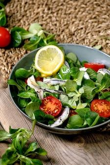 Insalata di campo verde con acciughe in salamoia o filetto di sarde e pomodorini, servita in una ciotola blu con limone e olio d'oliva su un tovagliolo di paglia sul vecchio tavolo di legno.