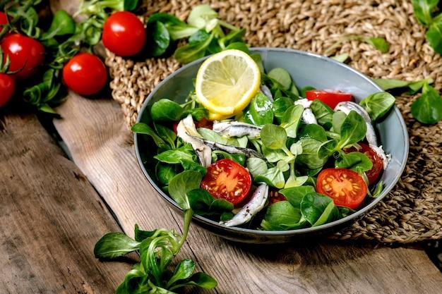 Insalata di campo verde con acciughe sottaceto o filetto di sarde e pomodorini, servita in una ciotola blu con limone e olio d'oliva su un tovagliolo di paglia sul vecchio tavolo di legno