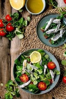 Insalata di campo verde con filetto di acciughe o sarde in salamoia e pomodorini, servita in una ciotola blu con limone e olio d'oliva