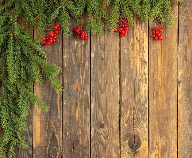Rami di abete verde e bacche rosse su fondo in legno. concetto di natale e capodanno. posto per il tuo testo.
