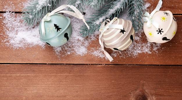 Abete verde con giocattoli e neve su fondo in legno