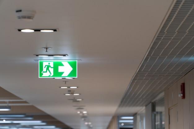 Caduta verde del segno di uscita di sicurezza sul soffitto nell'ufficio.
