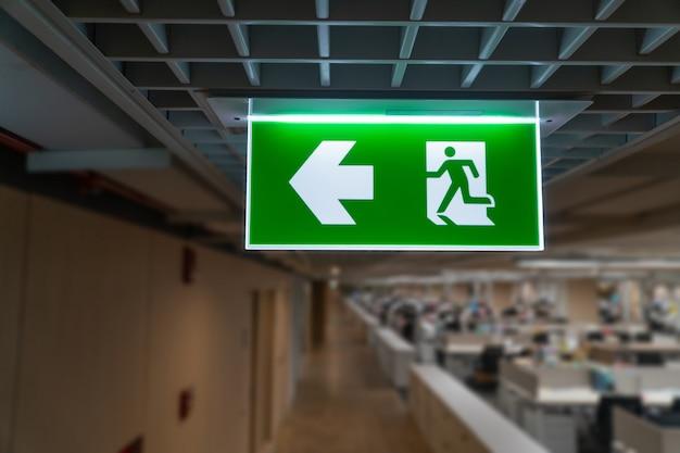 Il segno verde dell'uscita di sicurezza appende sul soffitto nell'ufficio.