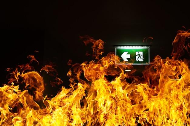 Il cartello verde dell'uscita antincendio è appeso al soffitto del magazzino. il concetto di addestramento antincendio e preparazione per l'evacuazione