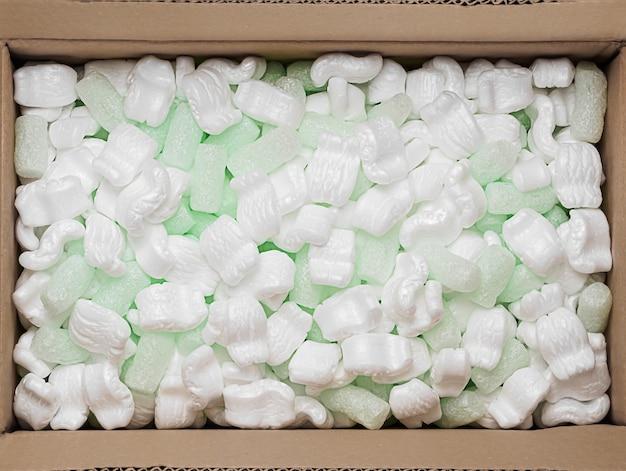 Riempitore di trucioli di gomma piuma verde e polistirolo bianco in una scatola di cartone per l'imballaggio