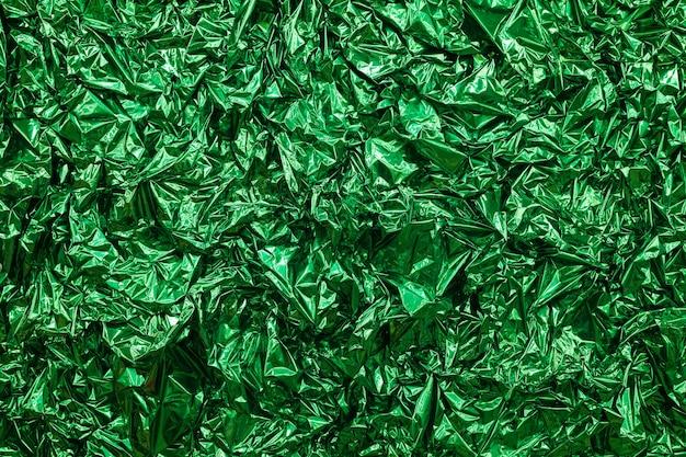 Sfondo di lamina verde con superficie stropicciata lucida per lo sfondo della trama