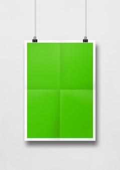 Poster piegato verde appeso a un muro bianco con clip. modello di mockup vuoto