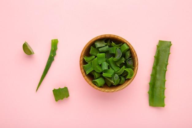 Foglia di aloe vera fresca verde in ciotola di legno su sfondo rosa. pianta medica naturale a base di erbe, cura della pelle, concetto di spa per la salute e la bellezza. vista dall'alto