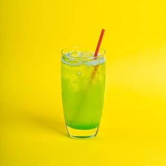 Succo di frullato di cocktail fresco verde in vetro con ghiaccio su sfondo giallo bevanda vitaminica detox