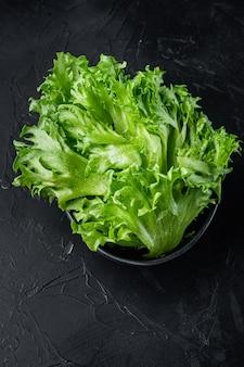 Foglie fresche di lattuga fresca verde, su sfondo nero