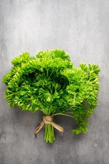 Prezzemolo verde e fresco sulla superficie metallica grigia.